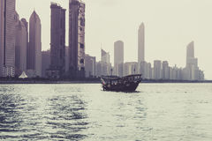 Abu Dhabi buildings skyline with old fishing boat. On the front Stock Photography