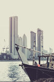 Abu Dhabi buildings skyline with old fishing boat. On the front Stock Image