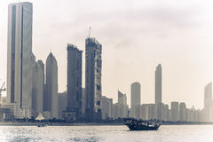 Abu Dhabi buildings skyline with old fishing boat. On the front Stock Images
