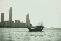 Abu Dhabi buildings skyline with old fishing boat. On the front Royalty Free Stock Photos