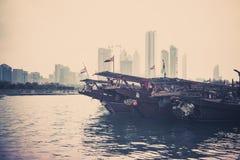 Abu Dhabi buildings skyline with old fishing boats Stock Image