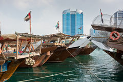 Abu Dhabi buildings skyline with old fishing boats. Old fishing boats in Abu Dhabi, UAE. Overcast day Stock Photos