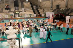 Abu Dhabi Chess Festival. Chess tournament held on the green court inside door Al Jazira Stadium Hall, children, women, young and old man playing together Stock Photos
