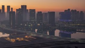 Abu Dhabi city skyline with skyscrapers before sunrise from above night to day timelapse. Abu Dhabi city skyline with illuminated skyscrapers before sunrise from stock video