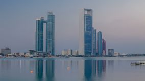 Abu Dhabi city skyline with skyscrapers before sunrise with water reflection night to day timelapse. Abu Dhabi city skyline with skyscrapers before sunrise with stock video