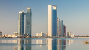 Abu Dhabi city skyline with skyscrapers after sunrise with water reflection timelapse. From the Breakwater near cultural village. Sun reflected on modern stock video