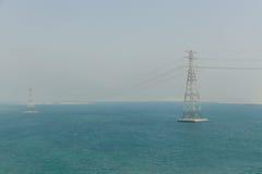 Abu Dhabi Cityscape mit Meer und elektrischen Beiträgen, UAE Lizenzfreies Stockfoto