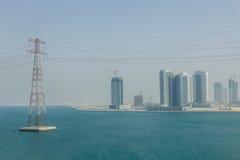 Abu Dhabi Cityscape mit Meer und elektrischen Beiträgen, UAE Stockbild