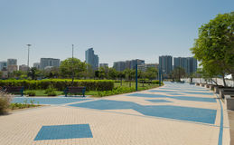 Abu Dhabi corniche. The corniche garden, the Abu Dhabi promenade. Skyline on the background royalty free stock image