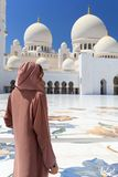 ABU DHABI, DE V.A.E - 11 MAART 2019: Vrouw met traditionele kleding van bruine kleur binnen Sheikh Zayed Mosque Verenigd Abu Dhab stock foto
