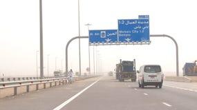ABU DHABI FÖRENADE ARABEMIRATEN - APRIL 3rd, 2014: Lastbilar som kör på en ökenmotorway i Förenadeen Arabemiraten med Royaltyfri Fotografi