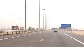 ABU DHABI FÖRENADE ARABEMIRATEN - APRIL 3rd, 2014: Lastbilar som kör på en ökenmotorway i Förenadeen Arabemiraten med Royaltyfria Bilder