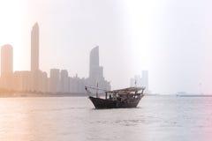 Abu Dhabi-Gebäudeskyline mit altem Fischerboot Stockfoto