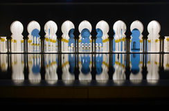Abu-Dhabi, Grand Moss columns and pole reflection by night. Architectural details of the famous religios building in the United Arabian Emirates Royalty Free Stock Photo