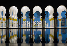 Abu-Dhabi Grand Moss, evening lights. Arches and columns with reflecting water surface about the famous white building in the United Arabian Emirates Royalty Free Stock Photos