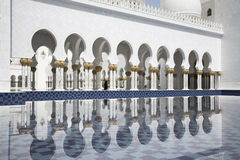 Abu-Dhabi, Grand Moss white arcades and water. Water surface reflection and gold ornamented columns Stock Images