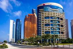 Abu Dhabi Highrises. Abu Dhabi Picturesque Breathtaking Highrises with Blue Windows and Palm Trees stock photo