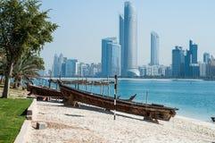 Abu Dhabi horisont plus tävlings- Dhows i forgrounden Fotografering för Bildbyråer