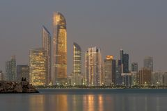 Abu Dhabi Seascape med skyskrapor i bakgrunden på aftonen royaltyfri fotografi