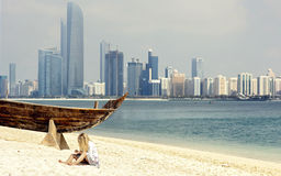 Abu Dhabi skyline from the beach. The girl sitting in the sand on the background of skyscrapers royalty free stock images