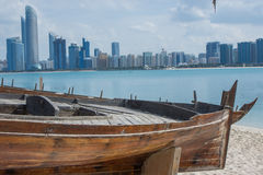 Abu Dhabi skyline from the Heritage Village, UAE. Abu Dhabi skyline from the Heritage Village, with old fishing boats in the foreground, United Arab Emirates Stock Image