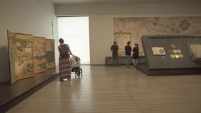People looking at exhibits in the new Louvre Museum in Abu Dhabi stock footage video. Abu Dhabi, UAE - April 04, 2018: People looking at exhibits in the new stock footage