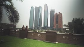Skyscrapers in Abu Dhabi view from the lawn of the hotel Emirates Palace stock footage video. Abu Dhabi, UAE - April 04, 2018: Skyscrapers in Abu Dhabi view from stock video footage