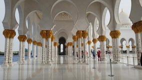 Abu Dhabi, UAE - 31 de marzo 2019 Gente en columnata con el ornamento floral de Sheikh Zayd Grand Mosque almacen de metraje de vídeo