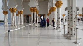 Abu Dhabi, UAE - 31 de marzo 2019 Gente en columnata con el ornamento floral de Sheikh Zayd Grand Mosque almacen de video