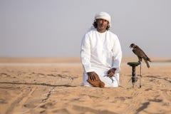 Man posing with his trained falcon. Abu Dhabi, UAE - Dec 15, 2017: Man in a traditional emirati dress proudly posing with his trained show falcon Stock Photos