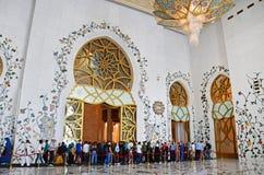 ABU DHABI UAE - MARS, 19, 2019: Folkinsida av den härliga ljuskronan i formen av en blomma i Sheikh Zayed Mosque royaltyfri fotografi