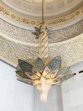 ABU DHABI UAE - MARS, 19, 2019: H?rlig ljuskrona i formen av en blomma i Sheikh Zayed Mosque inom royaltyfria foton