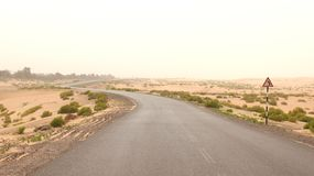 ABU DHABI, UNITED ARAB EMIRATES - APRIL 3rd, 2014: Desert beside of the main road with a street sign.  Stock Photography
