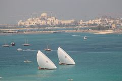 Abu Dhabi, United Arab Emirates. Close up view of the coast of Abu Dhabi, in the United Arab Emirates, with yachts sailing on the Gulf waters and palace under royalty free stock photography