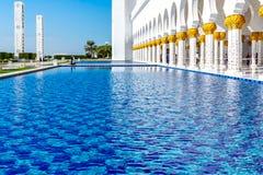 Abu Dhabi, United Arab Emirates - 13 de diciembre de 2018: piscinas de agua decorativas delante de la mezquita magnífica imagen de archivo libre de regalías