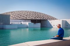 Abu Dhabi, United Arab Emirates, November 14, 2017, The Louvre,. Man sitting on a wall and looking across the water at the Louvre, Abu dhabi Stock Photography