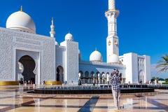 Abu Dhabi, Verenigde Arabische Emiraten - 13 December, 2018: het meisje bekijkt de voorgevel van de Grote moskee stock afbeelding