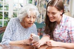A abuela adolescente de la nieta mostrando cómo utilizar Phon móvil Foto de archivo