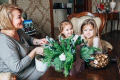 Abuela con dos childs que se preparan para la Navidad Foto de archivo libre de regalías