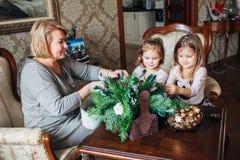 Abuela con dos childs que se preparan para la Navidad Fotos de archivo libres de regalías