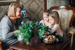 Abuela con dos childs que se preparan para la Navidad Imágenes de archivo libres de regalías