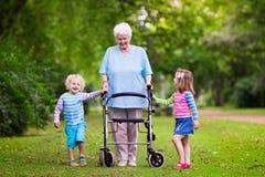Abuela con el caminante que juega con dos niños foto de archivo