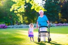 Abuela con el caminante y la niña en un parque Foto de archivo libre de regalías