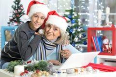 Abuela con el nieto que se prepara para la Navidad Foto de archivo