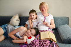 Abuela con sentarse sonriente de los nietos en el sofá Fotografía de archivo