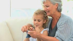Abuela con su hacer punto magnífico de la hija almacen de video