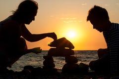 Abuela con su nieto en la playa en la puesta del sol imagen de archivo