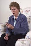Abuela dada una sacudida eléctrica sorprendida Texting en el teléfono celular Fotografía de archivo