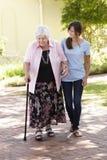Abuela de ayuda de la nieta adolescente hacia fuera en paseo Foto de archivo libre de regalías