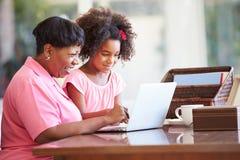 Abuela de ayuda de la nieta con el ordenador portátil Fotos de archivo libres de regalías